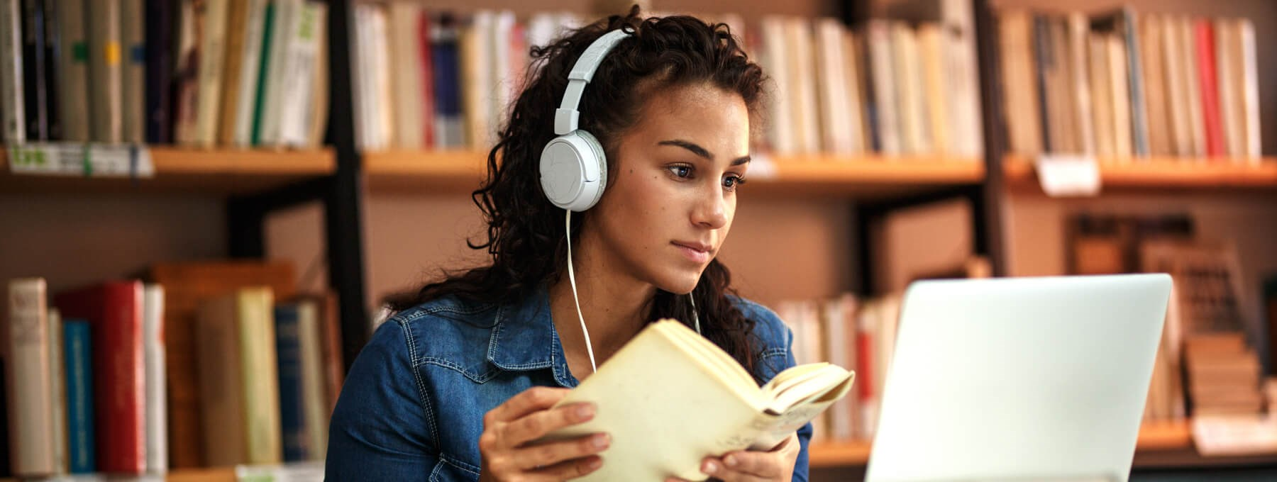 Student with Headphones referencing Book